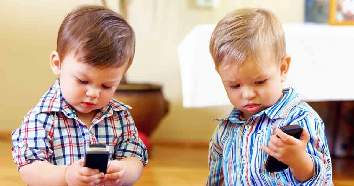 ВОЗ порекомендовала ограничить использование гаджетов детьми до 5 лет (two toddlers cellphone fb)